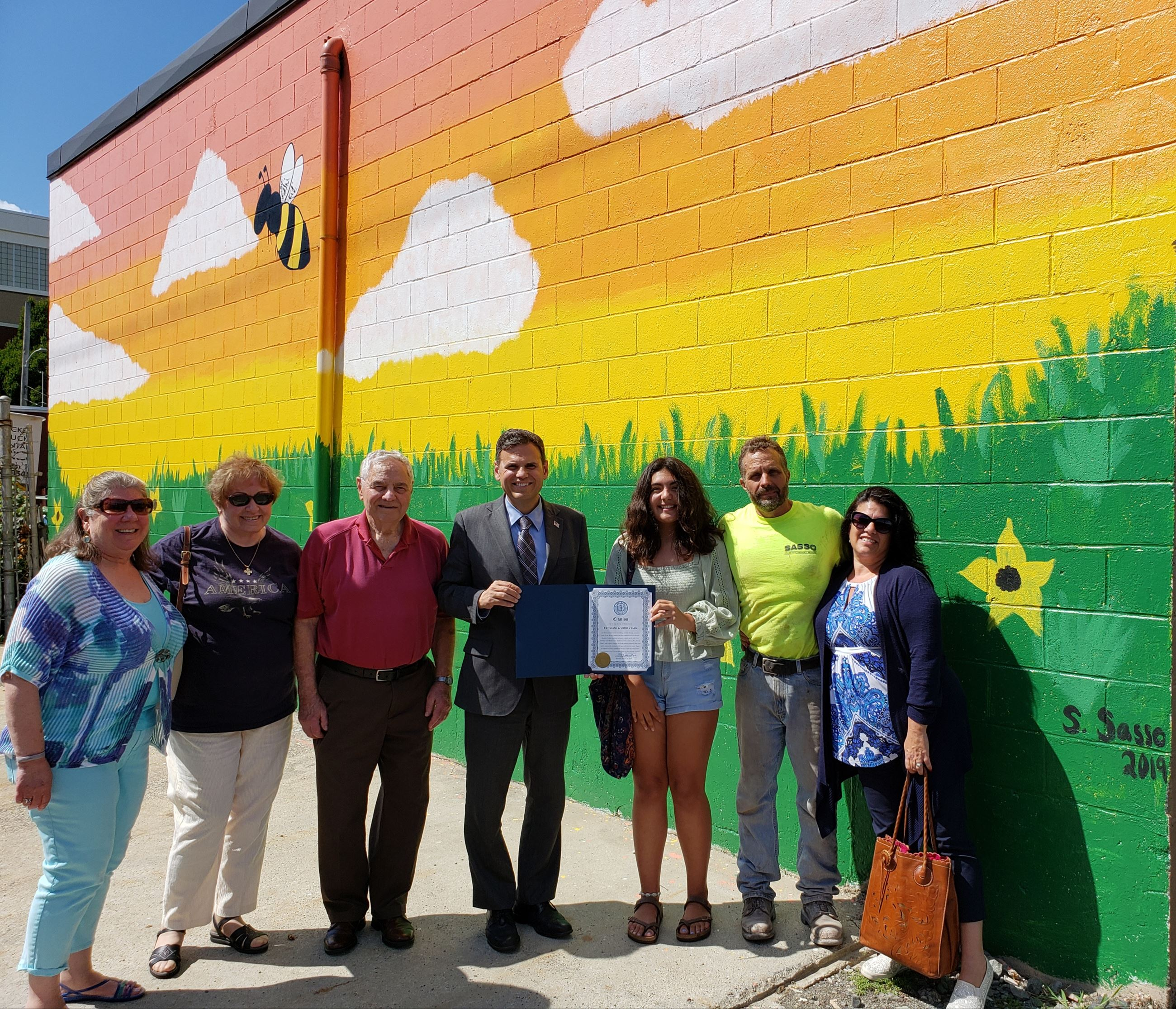 Mayor Christenson presents Sophia & Pat Sasso a citation in front of her mural at 15 Waite Court